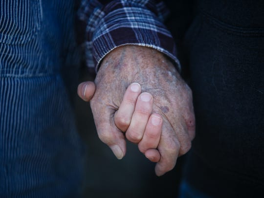 Bruce Brownlee, 91, holds the hand of his granddaughter