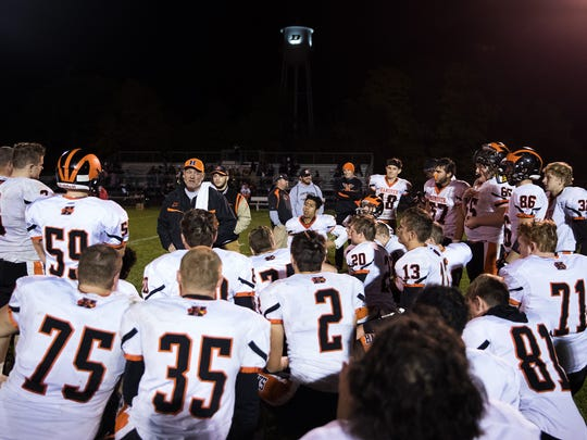 Hanover players listen to head coach Bill Reichart after winning a football game against Biglerville in 2017.