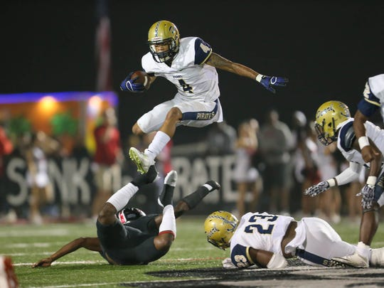 Pearl's Johnquarise Patterson (4) leaps over a Brandon defender during a first half carry. Pearl and Brandon played in an MHSAA Class 6A football game on Friday, November, 3, 2017 at Brandon High School. Photo by Keith Warren