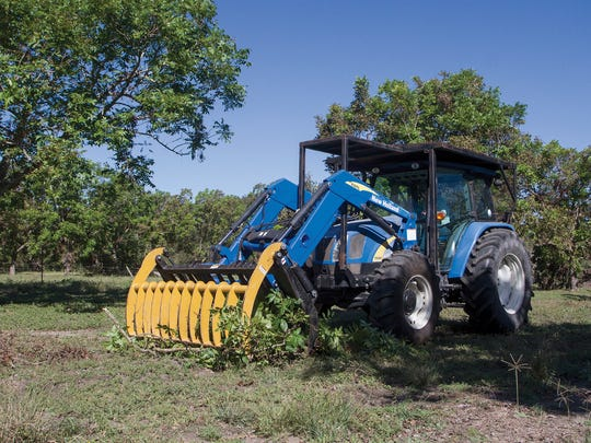 Jason West, of Dewitt M & J, uses a front end loader to pick up brush from John and L'Nell Starkey's pecan orchard in Thomaston, Texas. The Starkey's orchard suffered damage from Hurricane Harvey and lost 4 trees in the storm.