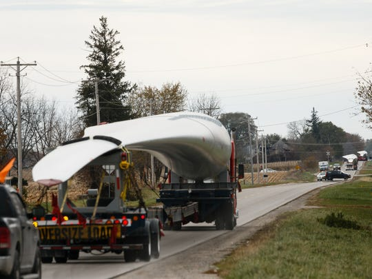 Trucks leave the TPI Composites plant with windmill