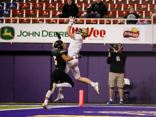 Iowa City, West's Austin Geasland (8) catches a pass over Bettendorf's Jalen Figgs (5) in the end zone to put West up 22-0 over Bettendorf during their 4A state semi-final football game at the UNI Dome on Friday, Nov. 10, 2017, in Cedar Falls. Iowa City, West would go on to win 23-0 to advance to the state finals.
