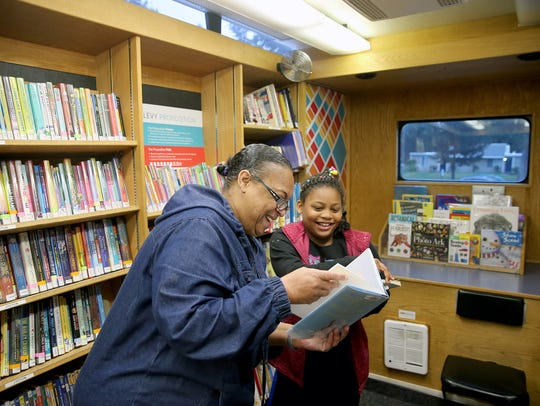 Renee and Da-Mira Thomas look at library books from
