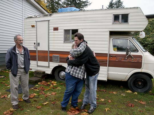 Sherry Green, center, is hugged by her son Bill Hahn outside of the RV she is living in with her husband John Green, left, in Port Orchard. The couple and the son are all homeless.
