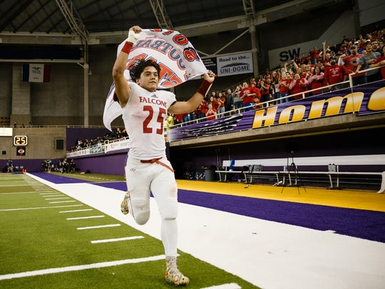 West Sioux, Hawarden's Victor Hernandez runs up and down the sideline with the state championship flag after their 35-14 victory over Hudson during their class A state final football game at the UNI Dome on Thursday, Nov. 16, 2017, in Cedar Falls.