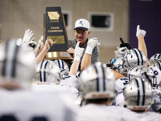 Xavier head coach Duane Schulte is hoisted onto his