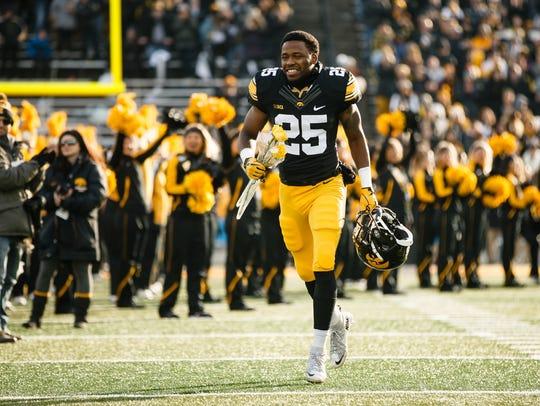 Iowa's Akrum Wadley (25) runs to greet his parents