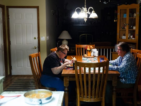 Holly Newvine, left, and Deb Robbins, right, eat dinner