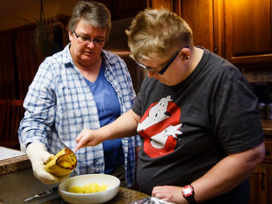 Holly Newvine, right, helps make dinner with Deb Robbins,