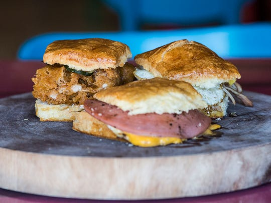 """November 27, 2017 - From left, the rooster, a fried chicken, pickle, tabasco honey biscuit, P Love's, a smoked bologna, American cheese and egg biscuit, and the CBQ, a bbq pork shoulder, egg, slaw and bbq sauce biscuit. Sunrise Memphis offers a variety of breakfast biscuits and plates as well as other options for breakfast. """"It's our twist on the classic favorites that your grandmother used to cook,"""" Ryan Trimm, chef and owner, said."""