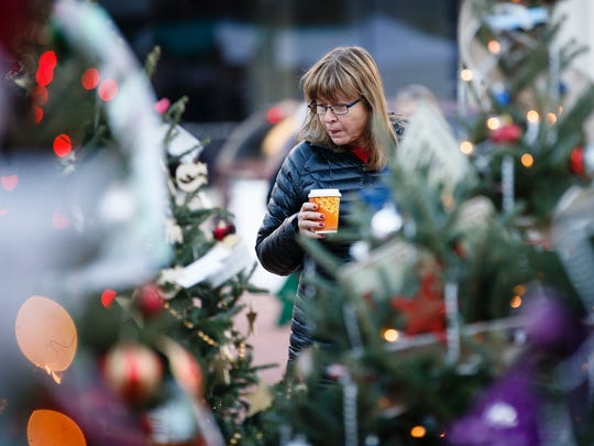 People walk around the Christkindlmarket Des Moines in Cowles Commons on Friday, Dec. 1, 2017, in Des Moines. The Market is a German-inspired Christmas market whose goal is to educate and entertain the community by exposing them to European-style foods, products and activities.
