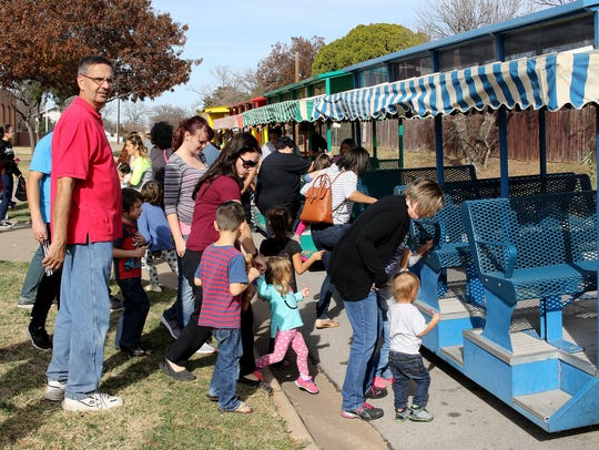 Families climb into the train for a ride at the Wichita
