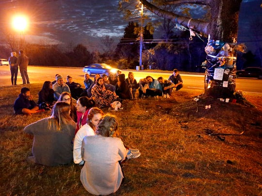 Siegel High School students gather near a tree along Memorial Blvd on Monday, Dec. 4, 201, to remember fellow Siegel student Will Divilbiss, who was killed late Saturday night, Dec. 4, 2017, in a wreck at the site.