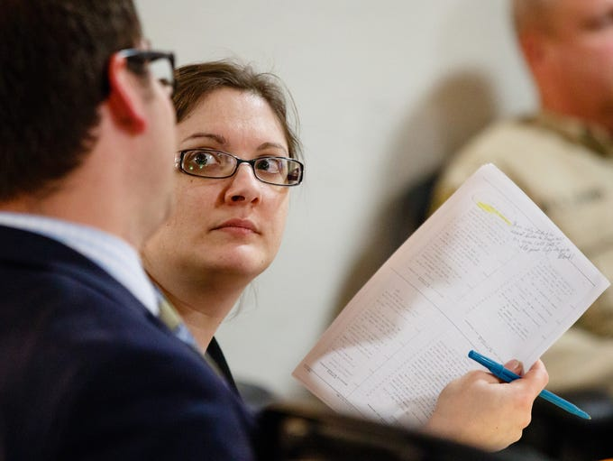 Nicole Finn shows attorney Thomas Augustine a note