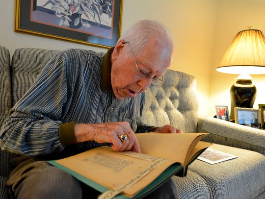 Don Peterson, 92, looks through an old scrapbook he's kept over the years of old newspaper clippings from the 1942-43 West York boys' basketball team he played on, the first championship team in program history. Monday, December 11, 2017. John A. Pavoncello photo