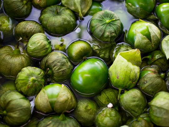 Tomatillos sit in a bath of vinegar before Carlos Hutchinson,