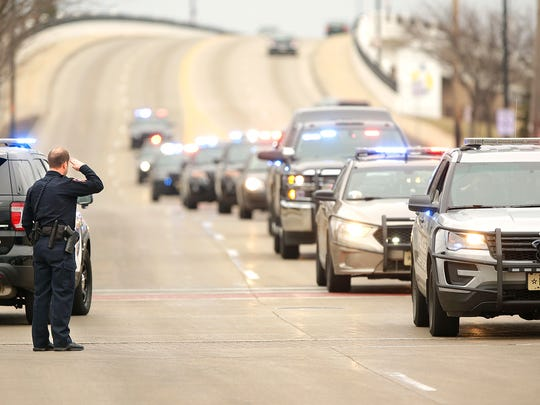 A City of Fond du Lac Police Officer salutes as a procession of police cars from Fond du Lac and Marathon counties go down Johnson Street in honor of Detective Jason T. Weiland of the Everest Police Department who was killed by a gunman Tuesday in Marathon County.