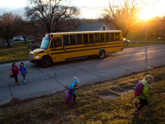 Sisters Sadi, 10, and Mayci Magnuson, 8, back, walk across the street as their two younger sisters, Aubri, 5, and Lilli, 6, bottom right, run up the hill after getting off the bus in front of their grandparents house  on Wednesday, Dec. 6, 2017, in Carbon. The four girls live with their grandparents and are the only children in town.