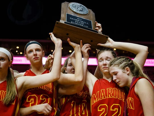 Marion holds up their runner up trophy after falling