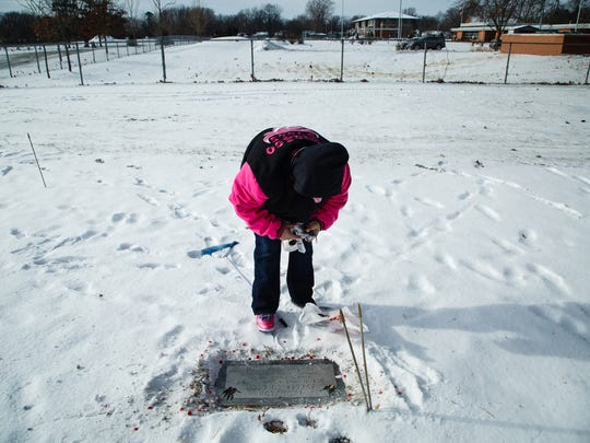 Mindy Shields, mother of Frederico Thompson, clears off his grave at the Glendale Cemetery on Saturday, Dec. 30, 2017, in Des Moines. Thompson was gunned down outside a nightclub early on New Year's Day last year.
