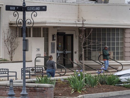 Pedestrians come and go from Porterville City Hall