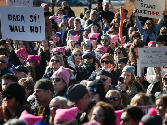 People gather in front of the Iowa State Capitol and listen as speakers talk during the Iowa Women's March on Saturday, Jan. 20, 2018, in Des Moines.