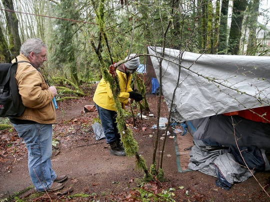 Doug Washburn, left, from the Kitsap County Department of Human Services, counts residents of a homeless camp located on a forested property on Almira Drive in East Bremerton. Agencies are working with residents of the camp to find shelter before the camp is cleared on Feb. 2.