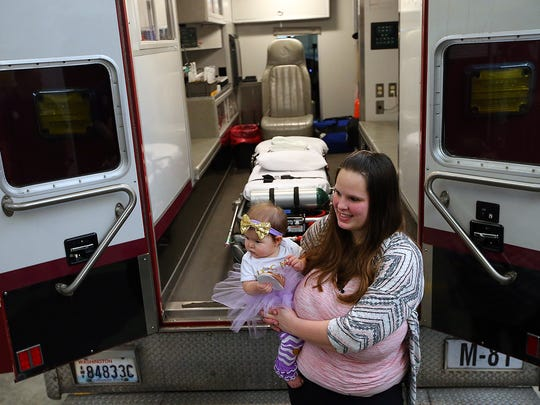 Lakeisha Rogers holds her one-year-old daughter Eleanor behind Medic 81 at North Kitsap Fire & Rescue Headquarters Station 81 in Kingston on Tuesday. The Rogers family stopped by the station to celebrate Eleanor's first birthday with the first responders who were there to deliver her.