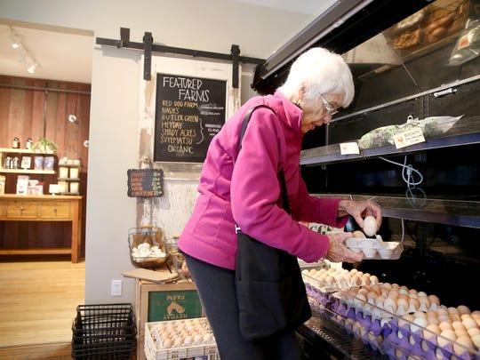 Wendy Reid of Bainbridge Island picks out eggs at Heyday Farm Store on Tuesday.