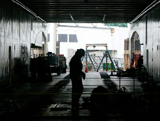 Washington State Ferries crew members work on the car deck of the Hyak.