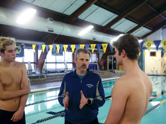 Bainbridge High School swim coach Kaycee Taylor, center, talks with Will Thompson, left, and Garrett Waite during practice Tuesday. This is Taylor's first season back with the Spartans after stepping down in 2015 to battle cancer.