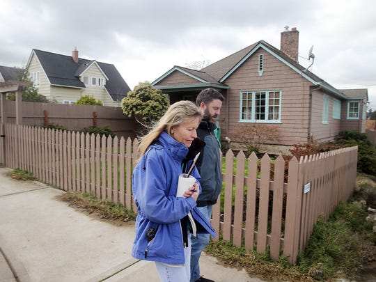 Julie Johnson and Jeffrey Coughlin walk past a home Johnson owns as a rental in  Bremerton home built in 1918.