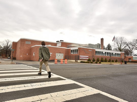 A student crosses the street at Nutley Senior High School, closed for a day following an online threat.