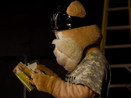 Jackson Generals Mascot Sarge reads a book on stage at Community Montessori before the school's character parade celebrating Read Across America Week