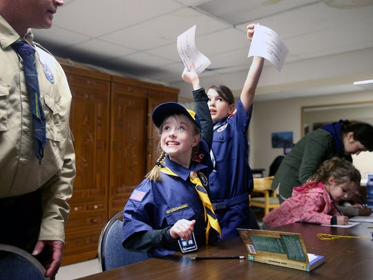 Brianna Richie and Sydney Taylor, both 8, celebrate completion of a project assignment during a recent Cub Scout meeting.