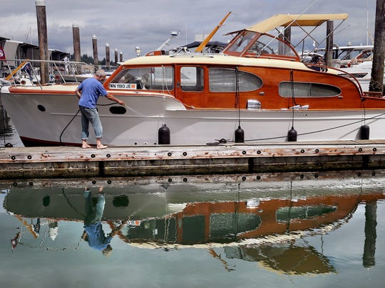 Photos by Larry Steagall / Kitsap Sun Top: Joe Cable of Ballard cleans his Chris Craft boat at the Port Orchard Marina on Thursday. He brought his 34-foot, 1952 boat over for the 28th annual Chris Craft Rendezvous, which continues Friday and Saturday. About 80 of the unique-looking boats are in town for the annual event. For information, go to www.chriscraftrendezvous.com. Left: Tom Demick of Brownsville ties up his 42-foot Chris Craft at the Port Orchard Marina on Thursday with the help of Brian Petersen, also of Brownsville. Joe Cable, of Ballard, cleans his Chris Craft boat at the Port Orchard Marina on Thursday. He brought his 34-foot, 1952 boat over for the 28th annual Chris Craft Rendezvous, which continues Friday and Saturday. About 80 of the unique-looking boats are in town for the annual event. For information, go to www.chriscraftrendezvous.com.