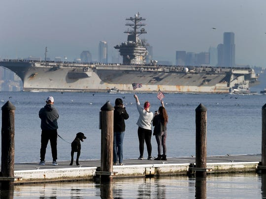 The USS Nimitz returns from a deployment as people wave from the Manchester Pier on Sunday.  photos by Larry Steagall / Kitsap Sun The USS Nimitz returns from a deployment as people wave from the Manchester Pier on Sunday.