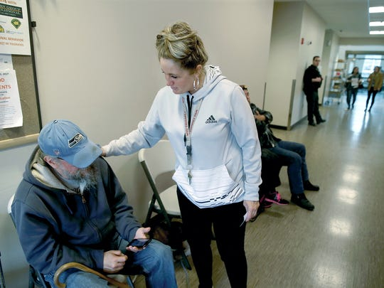 Michelle Fleetwood, the shelter manager at the Salvation Army in Bremerton, greets Les Rhoads, a winter shelter resident, on Friday.The shelter residents were sleeping on the hallway floor.
