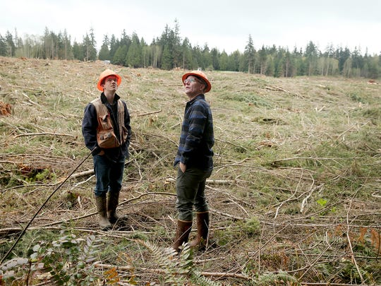 Griffin Chamberlin and Mike Mackelwich, both with Pope Resources, at a timber harvest site near Hansville in April. Herbicide planned to be sprayed there is intended to give seedling trees the best chance at survival.