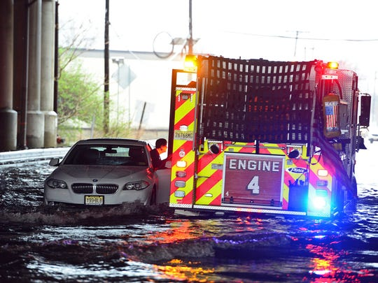 A Hackensack Fire Engine rescues a driver from high waters on Green St in Hackensack on Monday morning April 16, 2018.