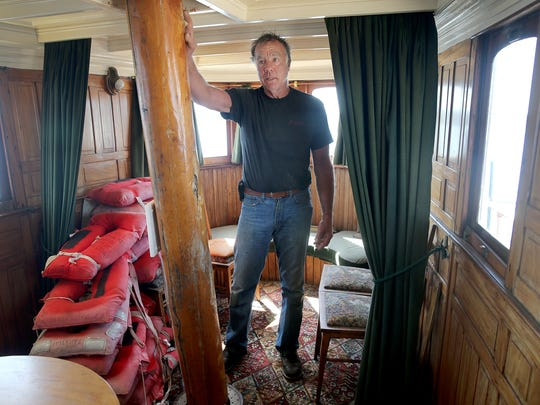 Christian Lint is inside the dining area on his historic boat El Primero, moored at the breakwater of the Bremerton Harborside Marina on Monday. Lint says if the port votes to prohibit moorage, he'll move his boats to a marina that allows public access.