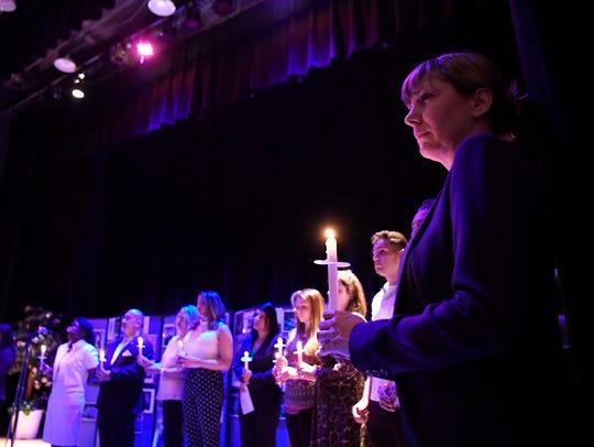 Candlelight vigil coordinator Joan Nixon, far right,