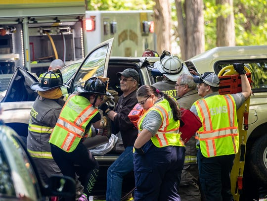 Crews work to extricate a patient from a vehicle at