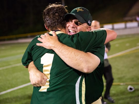 York Catholic head coach Shane Harper celebrates with York Catholic's Jarred Kohl (1) after winning the YAIAA Boys Lacrosse Championship game between York Catholic and Central York, Friday, May 11, 2018 in Red Lion. The York Catholic Irish came back from a 9-5 deficit at the half to win the championship 13-12 in overtime against the Central York Panthers.