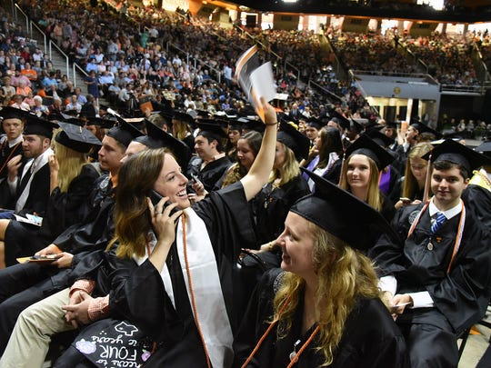 A UT graduate waves to her family at the University of Tennessee College of Arts and Sciences Commencement Ceremony at Thompson-Boling Arena on Saturday, May 12, 2018.