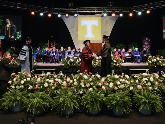 Graduates walk across the stage at the University of