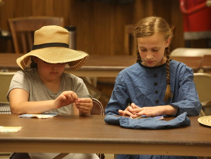Lillie Kruse and Ella Gable try their hands at quilting.