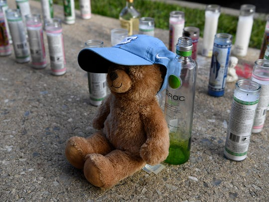 A stuffed bear and candles create a makeshift memorial