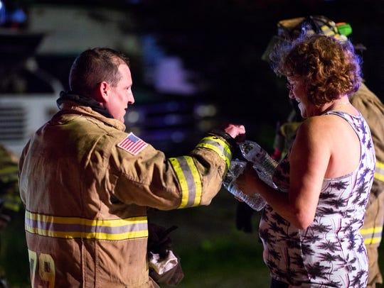 Neighbor Lona Rinehart gives water bottles to firefighters