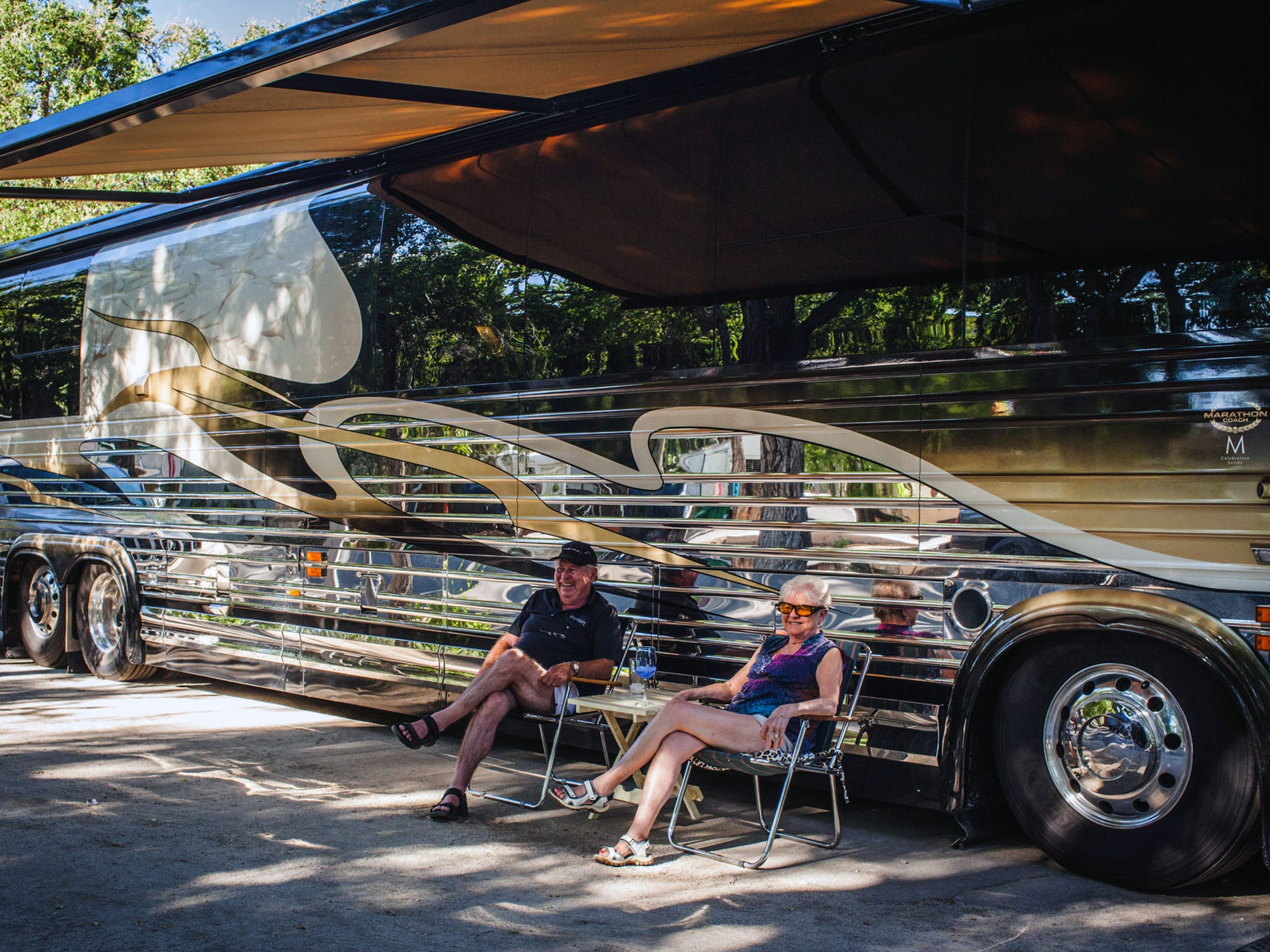 A couple sits outside their large bus-sized RV during